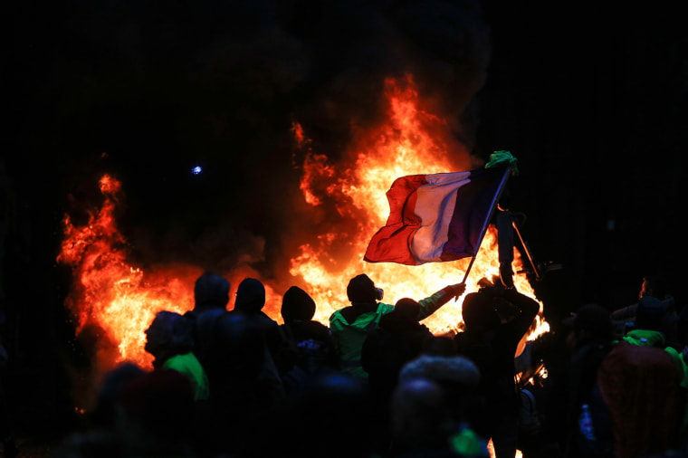 Image: Protestors fly a French flag during a protest of Yellow vests (Gilets jaunes) against rising oil prices and living costs