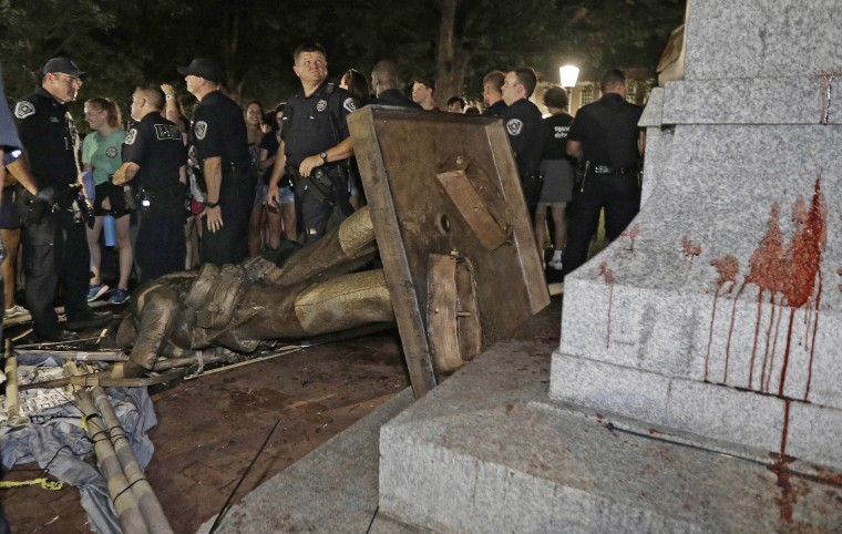 Image: Police stand guard after the confederate statue known as Silent Sam was toppled by protesters on campus at the University of North Carolina in Chapel Hill