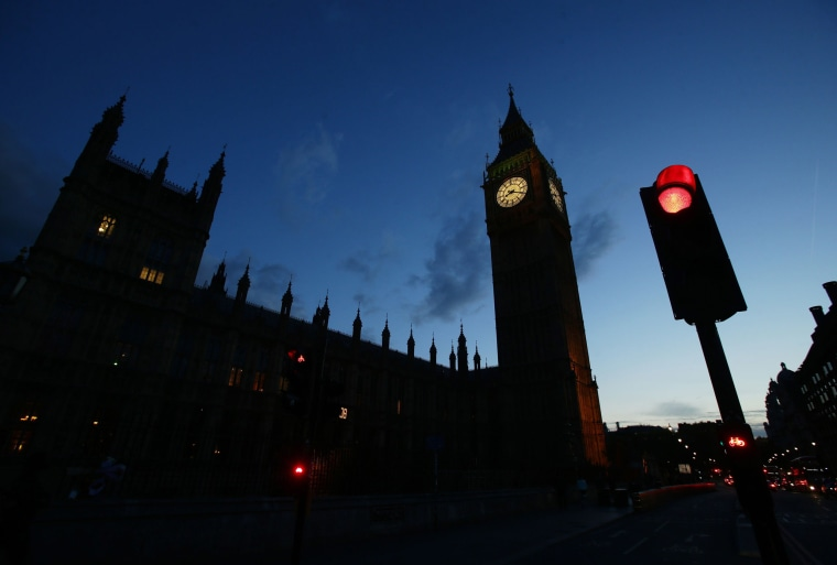 Image: A silhouette of the Houses of Parliament and Elizabeth Tower next to a red traffic light