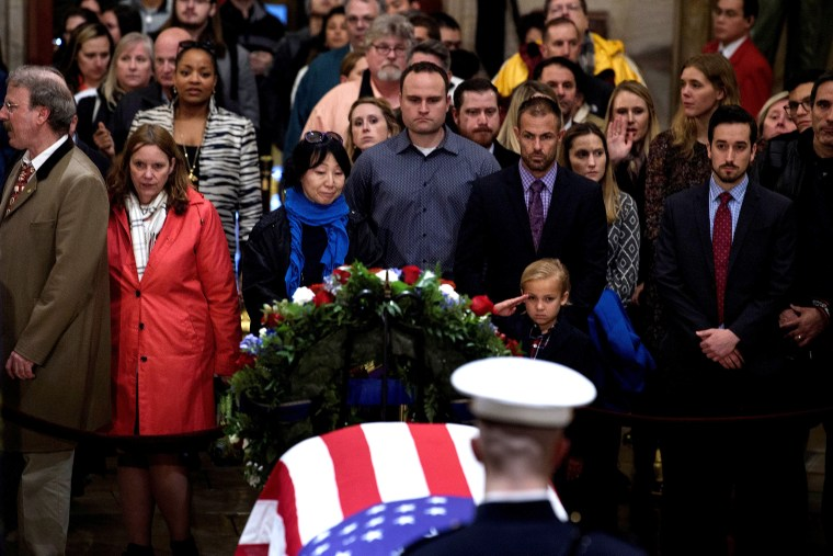 Image: Stephen G. Leighton Jr. salutes while paying respects with his father as the remains of former US President George H. W. Bush lie in state in the US Capitol's rotunda in Washington, DC
