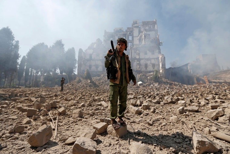 Image: Huthi rebel fighters inspect the damage after a reported air strike carried out by the Saudi-led coalition targeted the presidential palace in the Yemeni capital Sanaa