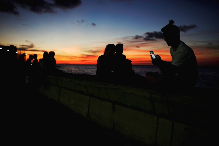 Image: A man looks at his phone at a hotspot along the seafront in Havana on July 14, 2018.