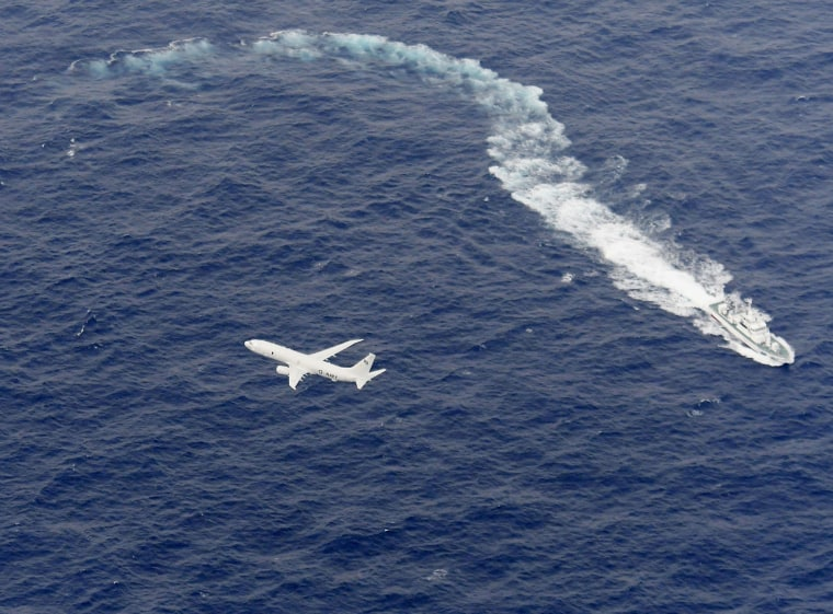 Image: A Japan Coast Guard patrol vessel and U.S. Navy airplane conduct search and rescue operation at the area where two U.S. Marine Corps aircraft have been involved in a mishap in the skies, off the coast of Kochi prefecture
