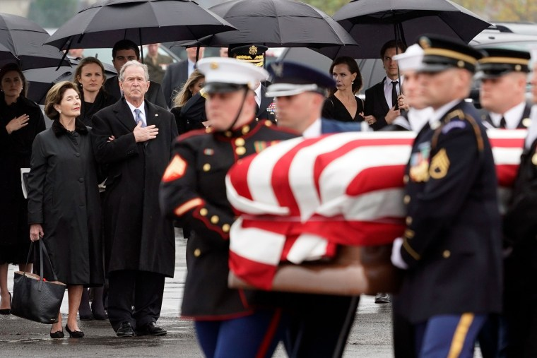 Image: Former President George W. Bush and former First Lady Laura Bush watch as the casket of former President George H.W. Bush is carried to a Union Pacific train following his funeral in Spring, Texas, on Dec. 6, 2018.