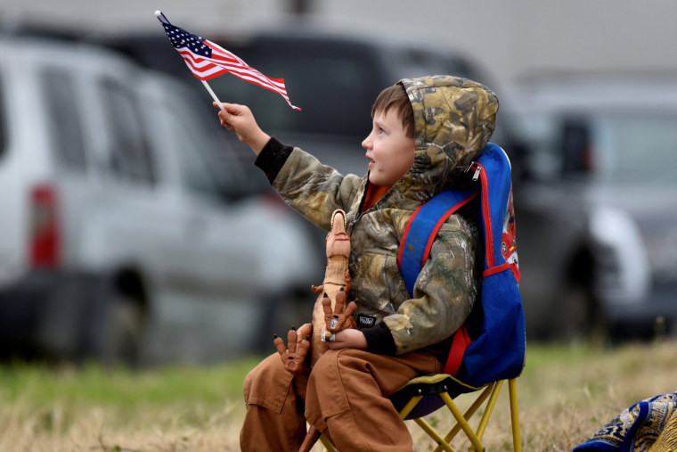 Image: A young boy waves an American flag as the funeral train passes through Navasota, Texas.