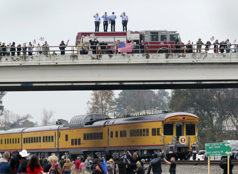 Image: Firefighters salute on an overpass as the funeral train carrying the casket of former President George H.W. Bush travels through Spring, Texas.