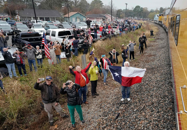 Image: People pay their respects as the train travels from Spring to College Station, Texas.