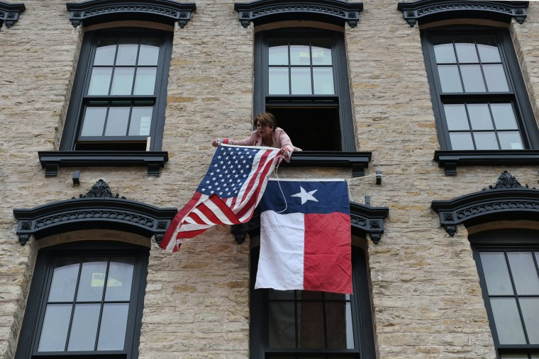 Image: Janice Scheve hangs flags from her building in Navasota, Texas.
