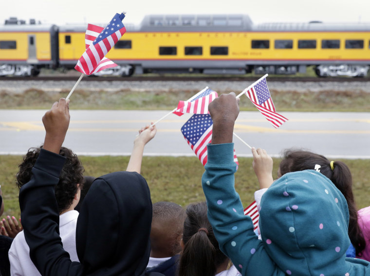 Image: Students from Salyer Elementary School wave flags as the train carrying the casket of former President George H.W. Bush travels through Spring, Texas.