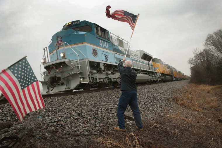 Image: Peter Olyniec waves a flag near Whitehall, Texas.