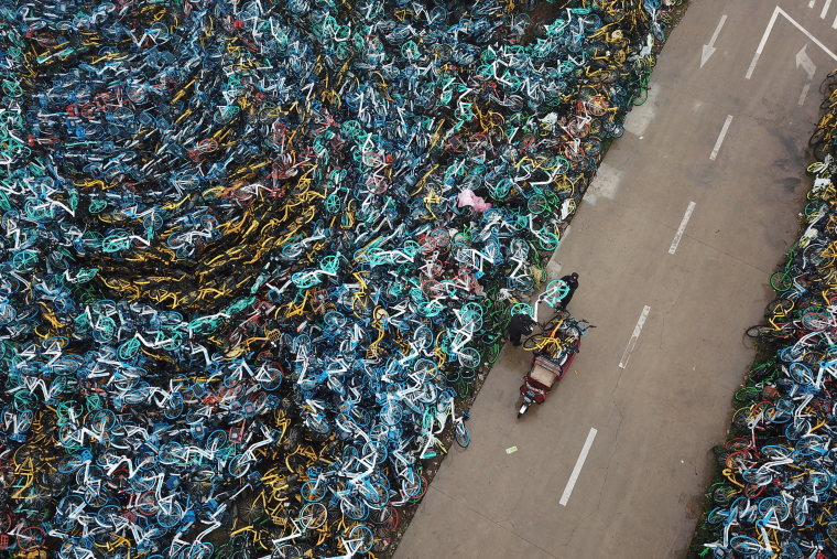 Image: Urban management officers transport a bicycle next to piled-up bicycles of bike-sharing services in Hefei