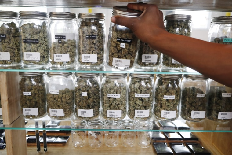 A clerk reaches for a container of marijuana buds for a customer at Utopia Gardens, a medical marijuana dispensary, in Detroit, on Oct. 2, 2018.