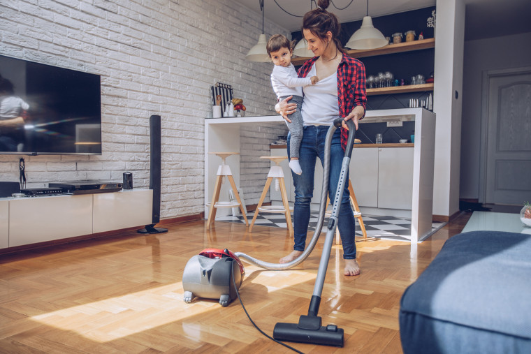 Image: Young woman using vacuum cleaner