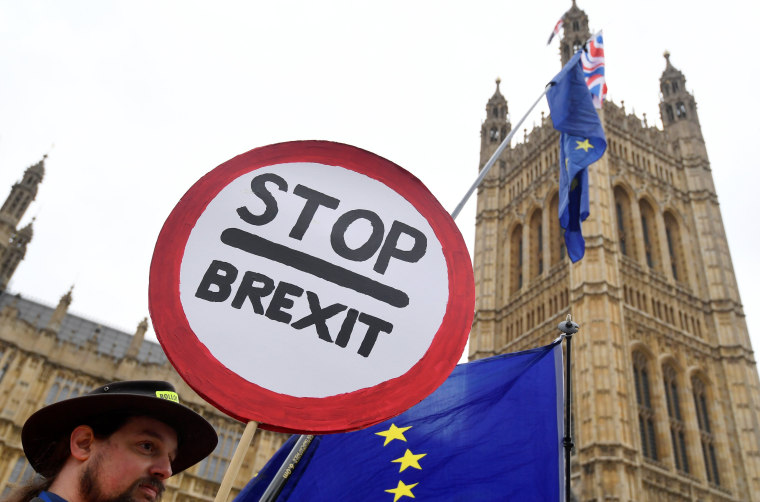 Image: Anti-Brexit protesters wave flags and placards opposite the Houses of Parliament in London