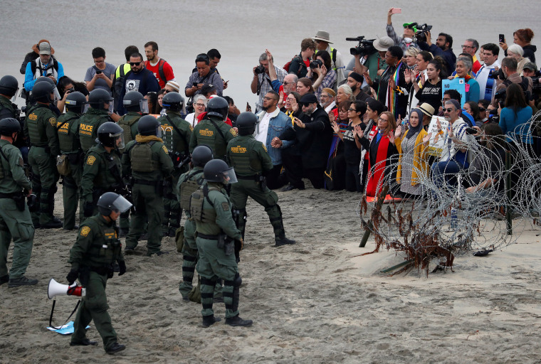 Faith leaders gather in support of the migrant caravan in front of U.S. Customs and Border Protection (CBP) officials, at the border fence between the United States and Mexico, as seen from Tijuana