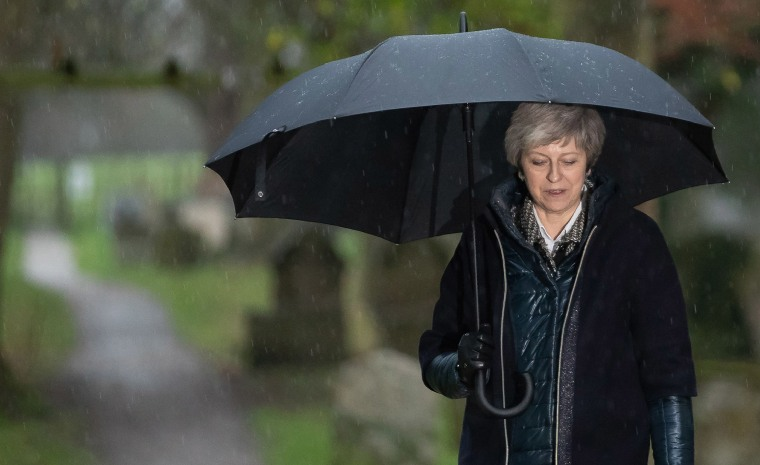 Image: Britain's Prime Minister Theresa May shelters from the rain under an umbrella after attending a church service near to her Maidenhead constituency