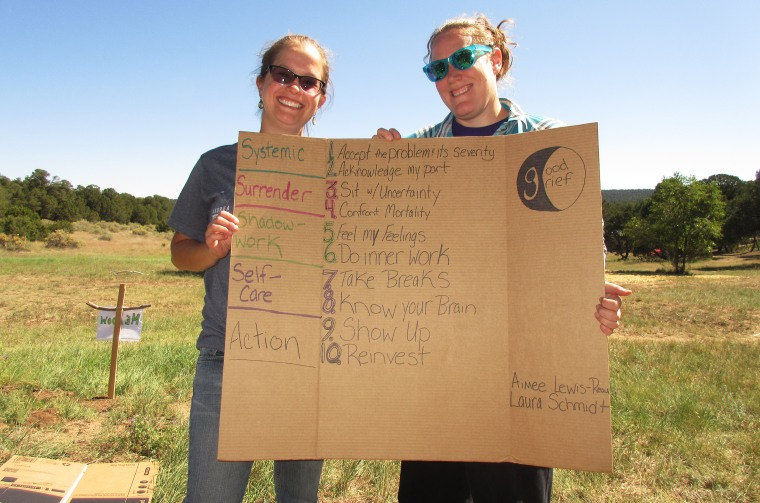 Aimee Reau, left, and LaUra Schmidt, creators of the Good Grief Network, hold a sign listing their 10 steps to deal with climate grief at the Uplift Climate conference in September.
