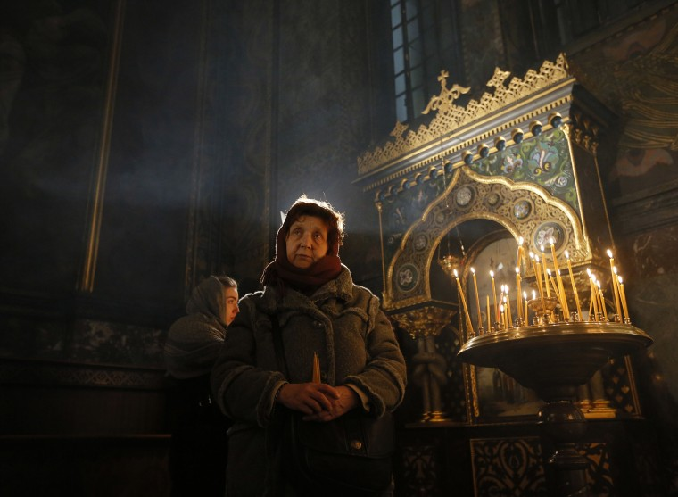 Image: Ukrainian Orthodox believers attend the Christmas Eve Mass in the St. Volodymyr Cathedral in Kiev,