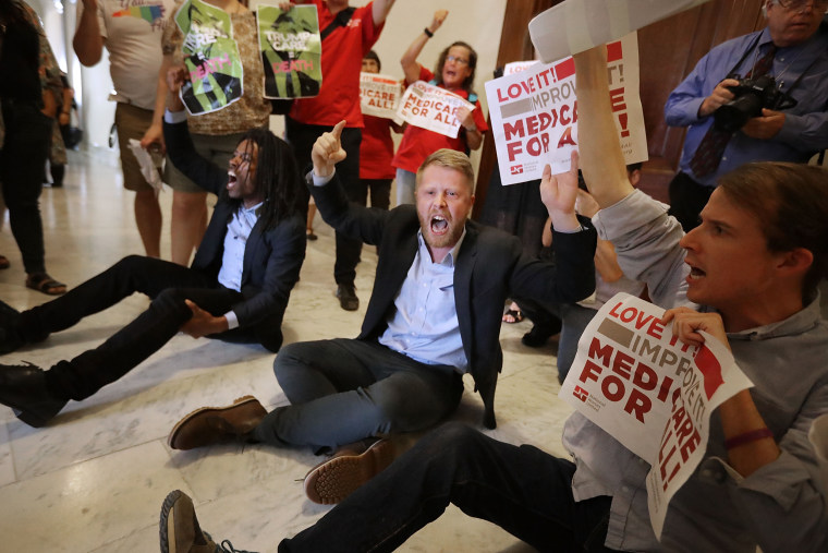"""Image: Demonstrators from Texas sit on the ground and chant, \""""Kill the bill, kill the bill,\"""" outside the offices of Sen. Ted Cruz while protesting against health care reform legislation on Capitol Hill on July 10, 2017."""