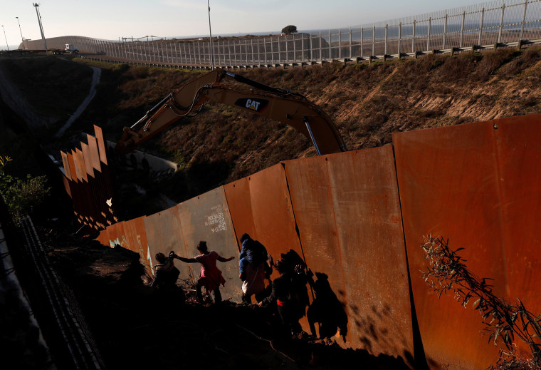 Image: Migrants climb down a steep hill after giving up on trying to climb the border wall into the U.S. from Tijuana