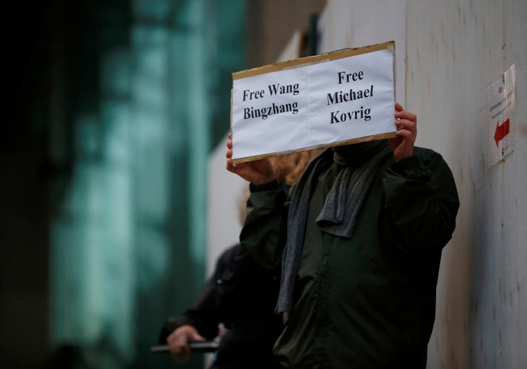 Image: A man holds a sign calling for China to release Wang Bingzhang and former Canadian diplomat Michael Kovrig, who was arrested in China, at the B.C. Supreme Court bail hearing of Huawei CFO Meng Wanzhou in Vancouver