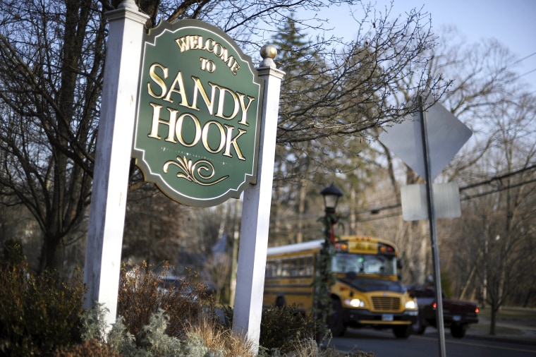 Image: A school bus drives past a Welcome to Sandy Hook sign in Newtown, Connecticut on Dec. 4, 2013.