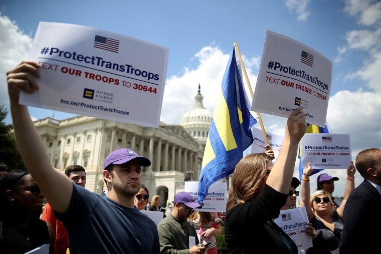 Image: Supporters hold signs at the Capitol condemning a ban on transgender service members in the military on July 26, 2017.