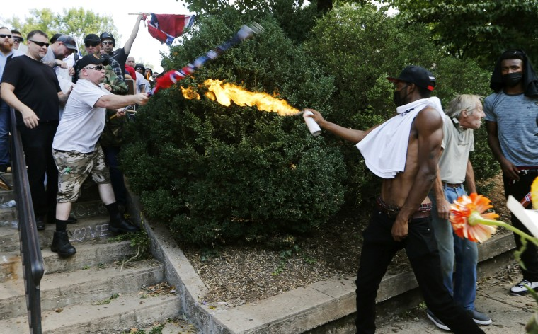 Image: A counter demonstrator uses a lighted spray can against a white nationalist demonstrator