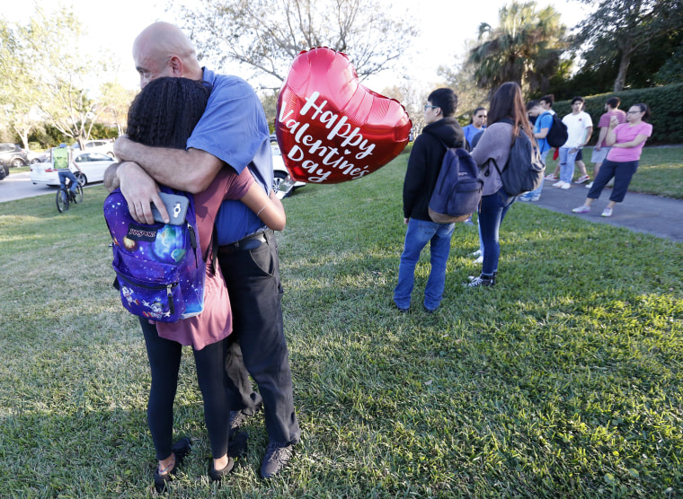 Image: Family members embrace following the shooting at Marjory Stoneman Douglas High School in Parkland, Florida.