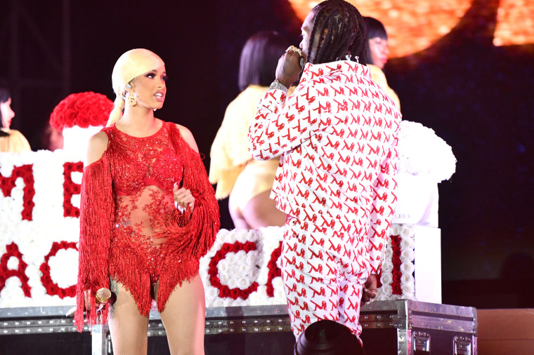 """Image: Cardi B reacts as Offset brings out flowers that read \""""Take Me Back Cardi\"""" during her show in Los Angeles on Dec. 15, 2018."""