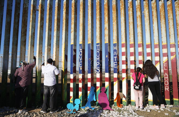 Image: Fernanda and Evelyne Lopez, right, speak with their father standing in San Diego on the other side of the border fence in Tijuana, Mexico, on Dec. 15, 2018.