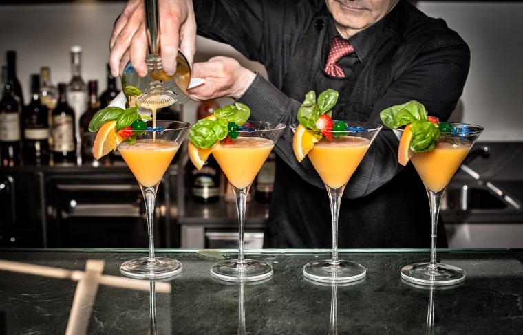 Image: Barman pouring cocktails, mid section