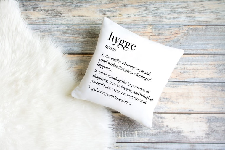 A faux fur throw and pillow donning the definition of hygge will be sure to keep you in the right headspace.