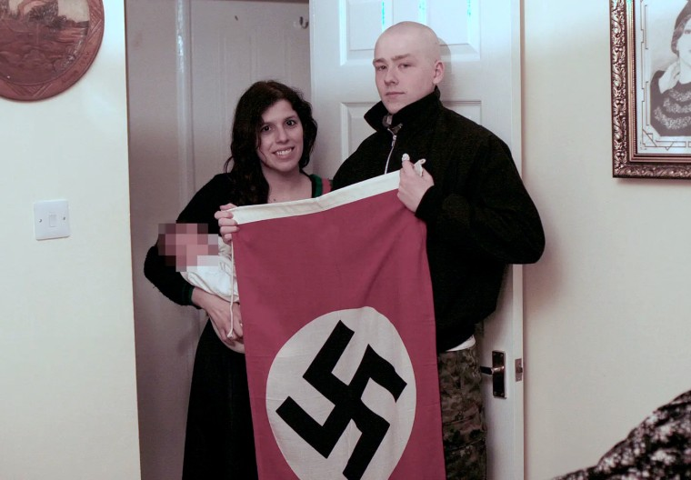 Image: Claudia Patatas and Adam Thomas pose with their son, whose middle name is Adolf.
