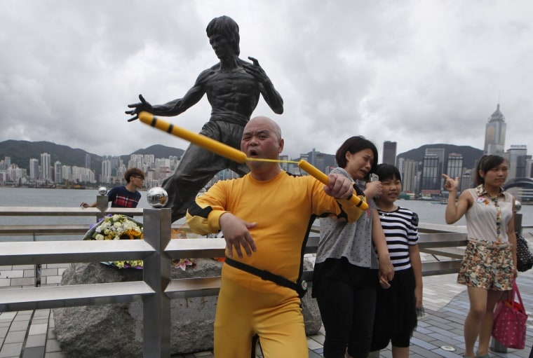 Image: A Japanese fan dressed as Bruce Lee shows his Nunchaku skills in front of a bronze statue of Lee in Hong Kong in 2013.