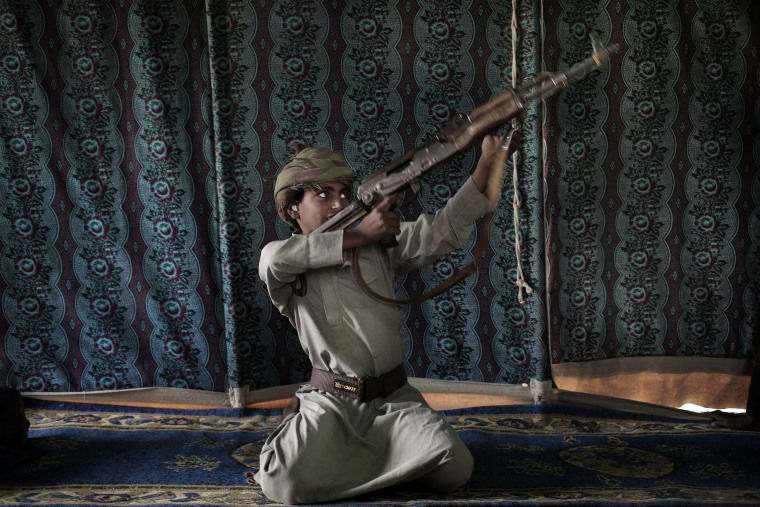 Image: Kahlan, a 12-year-old former child soldier, demonstrates how to use a weapon, at a camp for displaced persons where he took shelter with his family