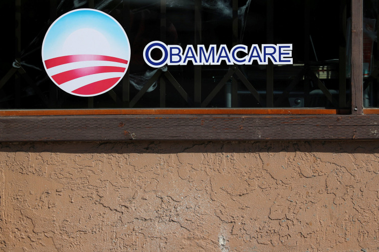 Image: A sign on an insurance store advertises Obamacare in San Ysidro