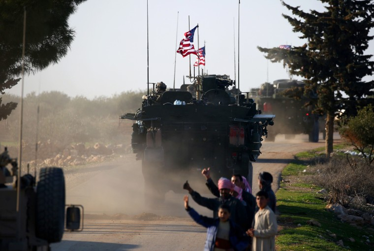 Image: A U.S. armored vehicles convoy drive near the village of Yalanli, Syria, on March 5, 2017.