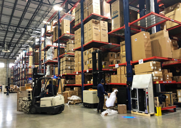 Image: Warehouse workers deal with inventory stacked up to the ceiling at an ABT Electronics Facility in Glenview