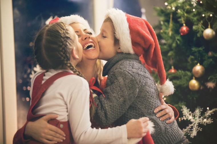 Children kissing mother on Christmas
