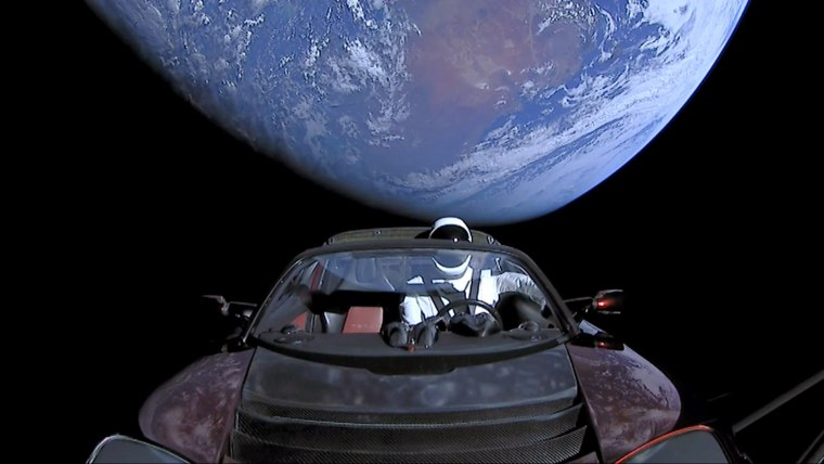 Image: A cherry red Tesla Roadster automobile floats through space after it was carried there by SpaceX's Falcon Heavy