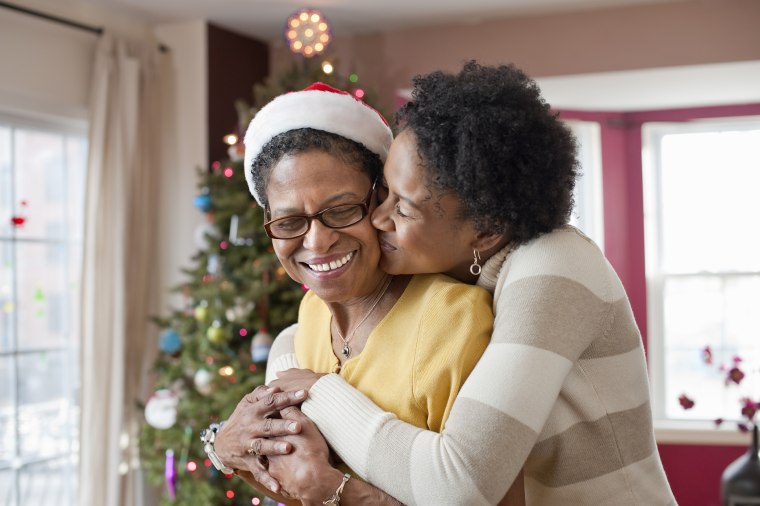 Image: Mom and adult daughter hugging at Christmas tree