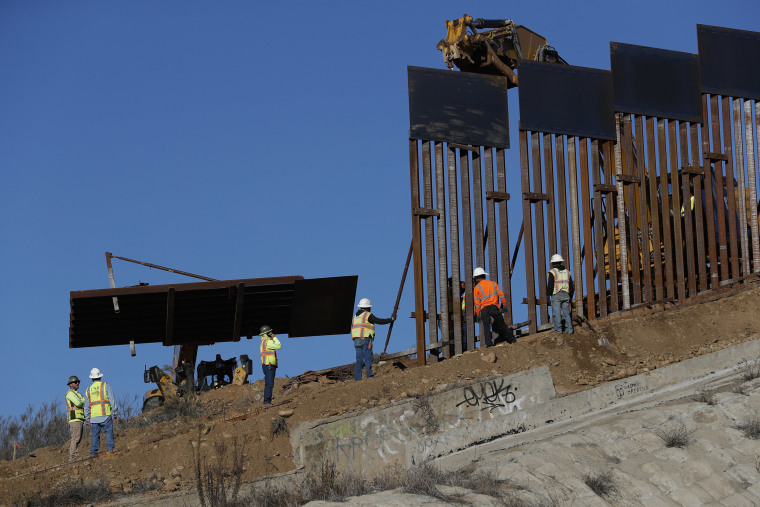 Image: Workers add new sections to the U.S. border wall, seen from Tijuana, Mexico