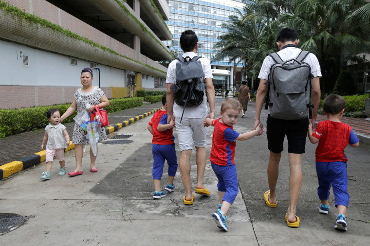 Image: An Hui, left, and his partner Ye Jianbin walk with their sons An Zhizhong, An Zhiya, and An Zhifei in Shenzhen, China, on Sept. 17, 2018.