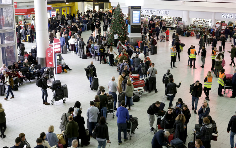 Image: Travelers wait in line at Gatwick Airport in London on Dec. 20, 2018.
