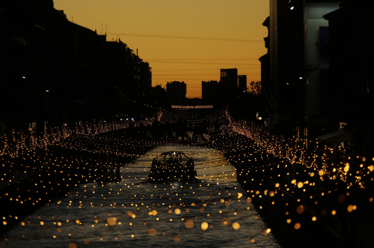 Image: A boat sails along the Naviglio canal decorated with Christmas lights
