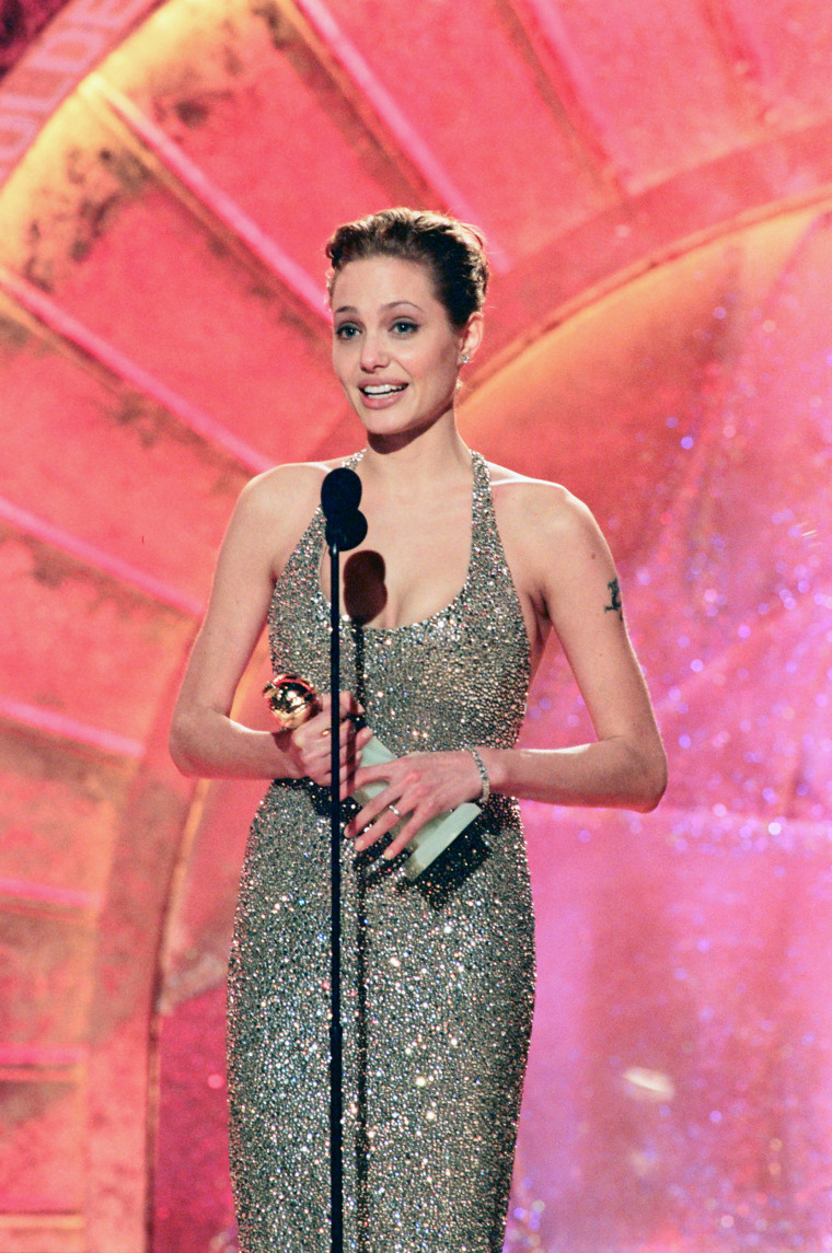 """56TH ANNUAL GOLDEN GLOBE AWARDS -- Pictured: Angelina Jolie, Best Actress In A Leading Role - Mini-Series Or Television Movie for \""""Gia\"""" on stage during the 56th Annual Golden Globe Awards held at the Beverly Hilton Hotel on January 24, 1999  (Photo by NBC/NBCU Photo Bank via Getty Images)"""