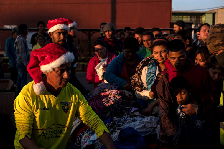 Image: Migrants, part of a caravan of thousands traveling from Central America to the United States, wait to receive gifts from an NGO outside of a temporary shelter in Tijuana, Mexico, on Dec. 24, 2018.