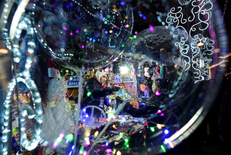 Image: A street vendor sells souvenirs at a Christmas fair in Saint Petersburg, Russia, on Dec. 23.