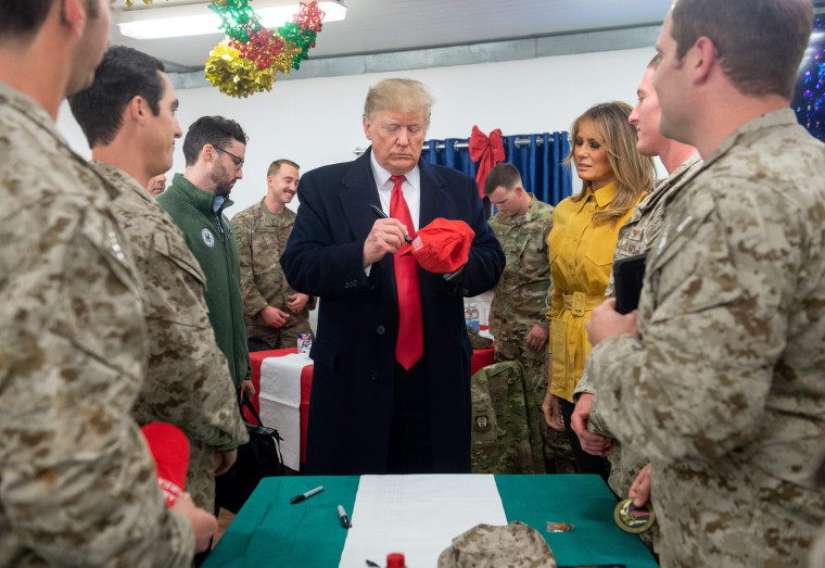 Image: President Donald Trump signs a hat at Al Asad Air Base in Iraq.